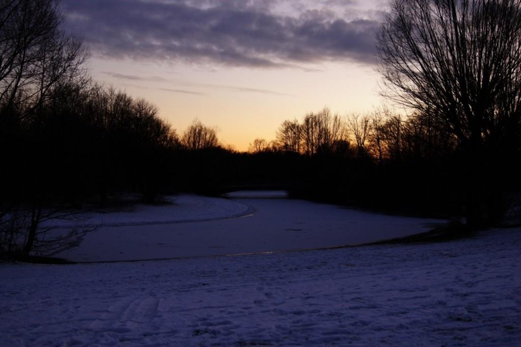 Bruecke ueber gefrorenem Bach bei Sonnenuntergang
