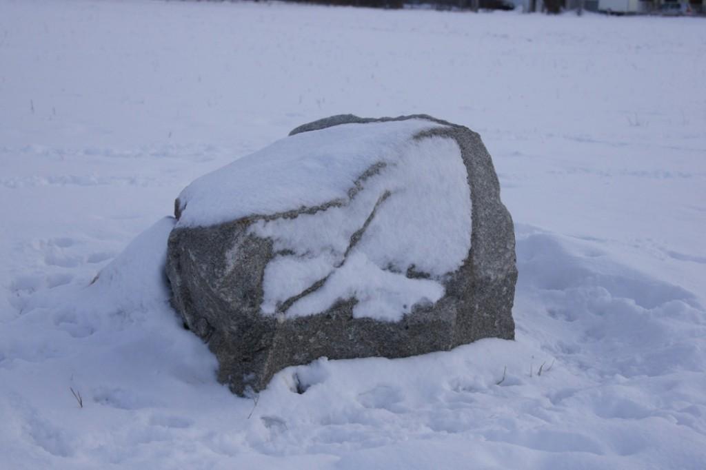 Fels im Schnee als Farbfoto
